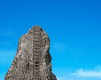 Rocky hill with wooden ladder in sky Royalty Free Stock Photos