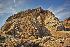 Rocky Hillside. A rocky, windswept hillside set against a vivid blue sky Stock Images