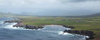Rocky Irish coast and houses in Dunquin on Dingle peninsula. Rocky Irish coast in Dunquin on Dingle peninsula in Ireland Stock Photo