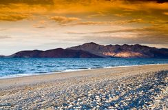 Rocky island. Colorful sunset on the sandy beach with mountainous islands in the background Royalty Free Stock Photo