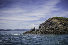 Rocky island with blue sky. In the sea Royalty Free Stock Images