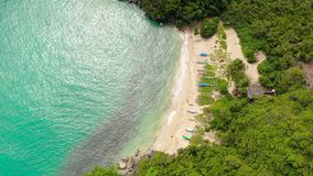 Rocky island with a jungle and a turquoise lagoon, aerial view. Caramoan Islands, Philippines. Small white sand beach. stock footage