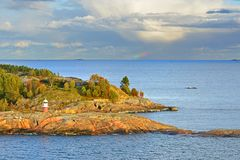 Rocky island with lighthouse of Helsinki archipelago at sunset. Distant rainbow in sea. Finland royalty free stock image