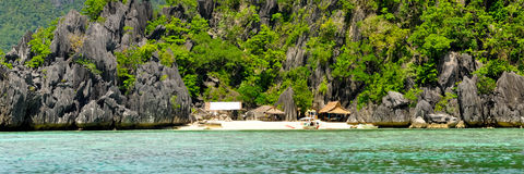 Rocky Island With Nipa Huts houses on a lonely Royalty Free Stock Photo