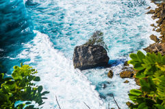 Rocky island with tree in the middle foamy waves. Uluwatu Bali Stock Photography