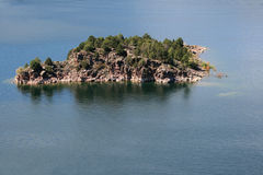 Rocky island with trees Stock Photos