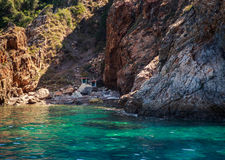 rocky island wall above azure sea with small buildings in gorge Stock Images