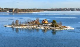 Rocky island with wooden house in Helsinki archipelago on sunny spring day. Finland Stock Photos
