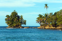 Rocky islet covered by tropical vegetation Stock Photos