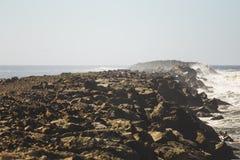 Rocky Jetty Hit vid havvågor arkivfoton
