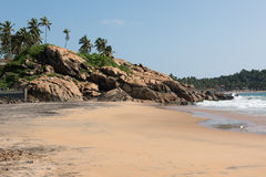 Rocky Kovalam Beach. Rocks at the sandy beach of Kovalam in Thiruvananthapuram, Kerala. A part of a beach resort is also seen with green trees. On the background stock image