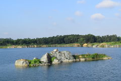 Rocky lake with small river islet Royalty Free Stock Photography