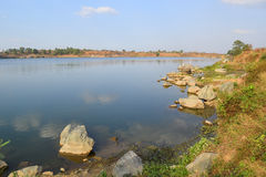Rocky lake with some stones and grass in the bank. Near Ho Chi Minh city, vietnam Royalty Free Stock Photo