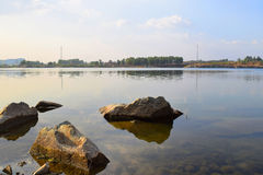 Rocky lake with some stones and grass in the bank. Near Ho Chi Minh city, vietnam Royalty Free Stock Image
