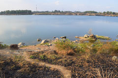 Rocky lake with some stones and grass in the bank. Near Ho Chi Minh city, vietnam Stock Image