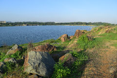 Rocky lake with some stones and grass in the bank. Near Ho Chi Minh city, vietnam Royalty Free Stock Images