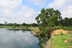 Rocky lake with some stones and grass in the bank. Near Ho Chi Minh city, vietnam Stock Photo