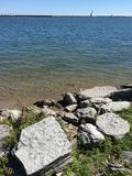 Rocky lakefront. Lakefront calm water front lake side boat inlet waves Stock Photos