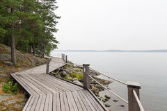 Rocky lakeshore with wooden pathway Royalty Free Stock Image
