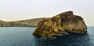 Rocky landscape, Gozo island Malta. Big rock in the Mediterranean sea at the entrance to the Dwajra Bay, on the coast of Gozo, Malta Royalty Free Stock Image