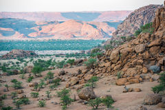 Rocky landscape of Namibia with huge boulders and green trees Stock Photography