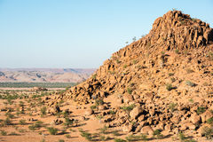 Rocky landscape of Namibia with huge boulders and green trees Royalty Free Stock Image