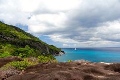Rocky landscape in the Seychelles with sailboat in the distance Stock Image