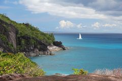 Rocky landscape in the Seychelles with sailing boat on the sea Stock Photography