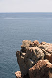 Rocky ledge. A rocky ledge overhanging the blue ocean of the Atlantic in Maine royalty free stock photo