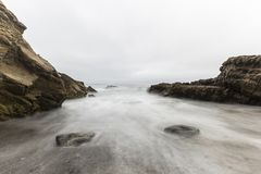 Rocky Malibu Beach with Motion Blur Water.  Royalty Free Stock Photography