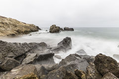 Rocky Malibu Beach with Motion Blur Water. Rocky Leo Carrillo State Beach with motion blur water in Malibu, California Royalty Free Stock Photo