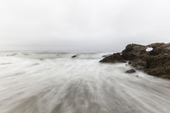 Rocky Malibu California Beach with Motion Blur Water Royalty Free Stock Image