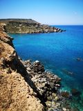 Rocky mediterranean seashore with azure and turquoise color water at Malta. Rocky mediterranean seashore with azure and turquoise color water, Malta, EU stock photography