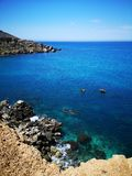Rocky mediterranean seashore with azure and turquoise color water at Malta. Rocky mediterranean seashore with azure and turquoise color water, Malta, EU royalty free stock photos