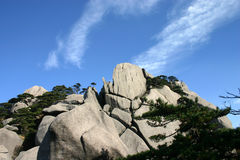 Rocky mountain. Bare rock and trees against blue sky Stock Photography