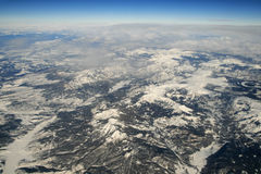 Rocky Mountain aerial photo. Aerial photograph of the Rocky Mountains in the winter with snow and some clouds extending to the horizon royalty free stock photography