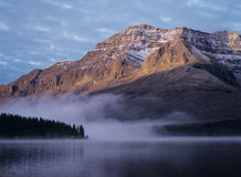 Rocky mountain fog over lake sunset royalty free stock photo