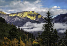 Rocky Mountain National Park with Fall Colors. The mountains of Rocky Mountain National Park, in Colorado, glow in the light of the rising sun, with the golden Royalty Free Stock Photography