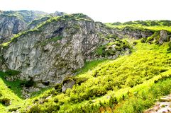 Rocky mountain slope covered with grass Royalty Free Stock Images