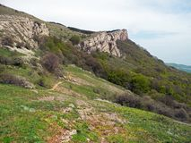 Rocky Mountain, sloping mountain ridge at spring. The forest covers the hills and hiking trail with people. Crimean mountains stock photo
