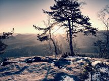 Rocky hill above inverse mist. Winter cold weather in mountains. Rocky mountain with snow cover and the Sun at horizon . Blue sky background stock images