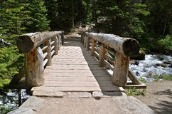 Rocky Mountain stream flows under bridge. A hiking path in the Rocky Mountain National Park area crosses a wooden bridge spanning a swift flowing stream Royalty Free Stock Photo