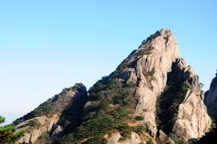 Rocky Mountain Summit on Huangshan. A tree covered rocky peak on top of Huangshan (Yellow Mountain) located in Anhui Province China on a cloudless blue sky Royalty Free Stock Images