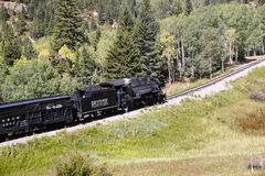 Rocky Mountain Train Adventure. Chama NM, USA, Sept. 19, 2017: A vintage steam locomoitve from the Cumbres & Toltec railroad climbs toward Chama Pass in early Stock Photos