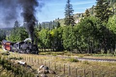 Rocky Mountain Train Adventure. Chama NM, USA, Sept. 19, 2017: A vintage steam locomoitve from the Cumbres & Toltec railroad climbs toward Chama Pass in early Royalty Free Stock Image
