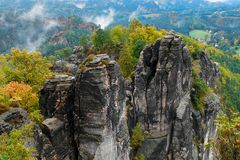 Rocky mountain view during autumn season. Foggy sunrise at Bastei, Saxon Switzerland, Germany stock photo