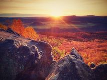 Rocky mountain with view into evening autumnal valley. Fantastic dreamy sunset on top of rocky mountain with view into evening autumnal valley. Mountain view Stock Images