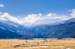 Rocky mountain view. Rocky mountain , grass field and blue sky with snow time in winter Stock Photos