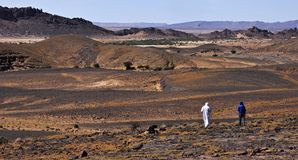 Rocky, mountainous hot and dry Sahara in Morocco with two outgoing people. Two men goes to the rocky, hot and dry Sahara Desert in Morocco Royalty Free Stock Photography