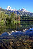 Rocky Mountains. Snow capped Rocky Teton Mountain ranges,The reflection of the colorful forests and mountains in the Taggart Lake.Grand Teton National Park Royalty Free Stock Images
